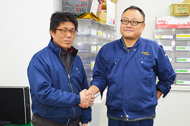 画像左 中尾 和宏 様  画像右 大南運送株式会社 業務部 課長代理 中島 誠 様 中島課長代理様が「これからも頑張ってください!」と、中尾様とがっちりと握手をしてくださりました。